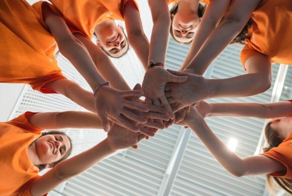 Mädchen stehen im Kreis und reichen sich die Arme