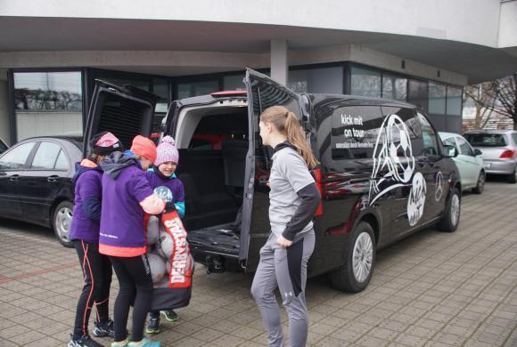Teilnehmerinnen laden kick mit Material aus dem Auto aus