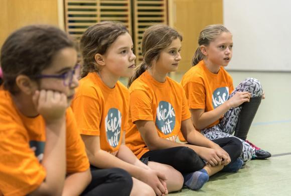 Vier Kinder sitzen am Boden und warten gespannt auf weitere Anweisungen.