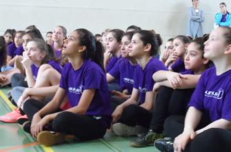 Mädchen sitzen am Boden und horchen aufmerksam zu