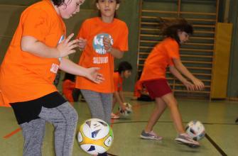 Mädchen spielen mit den Fußbällen